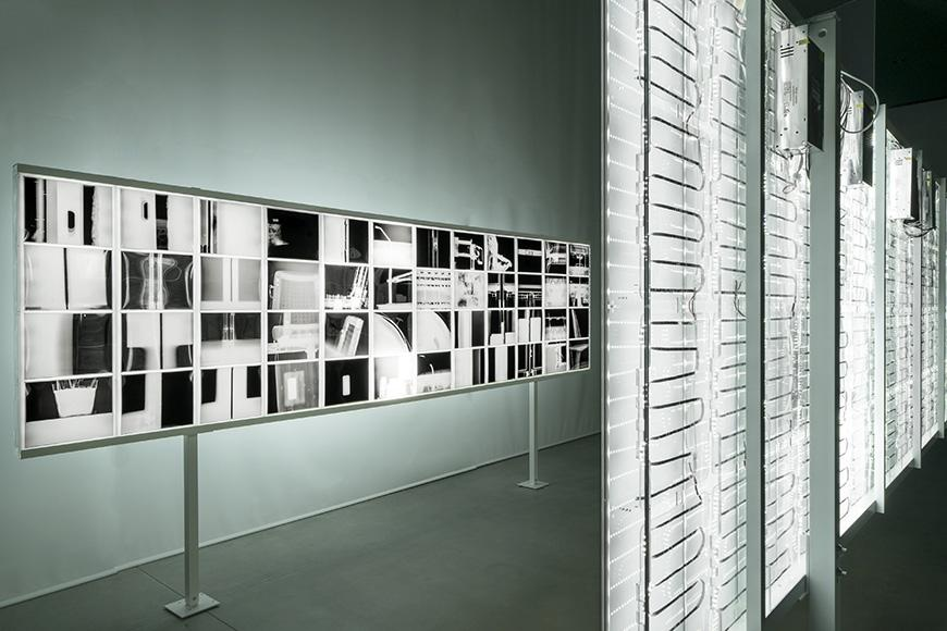 The interior of a modern monochrome gallery space dimly lit with white LED lights.