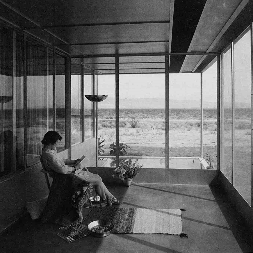 Black and white photograph of a woman seated and reading within a glass enclosed sun porch.