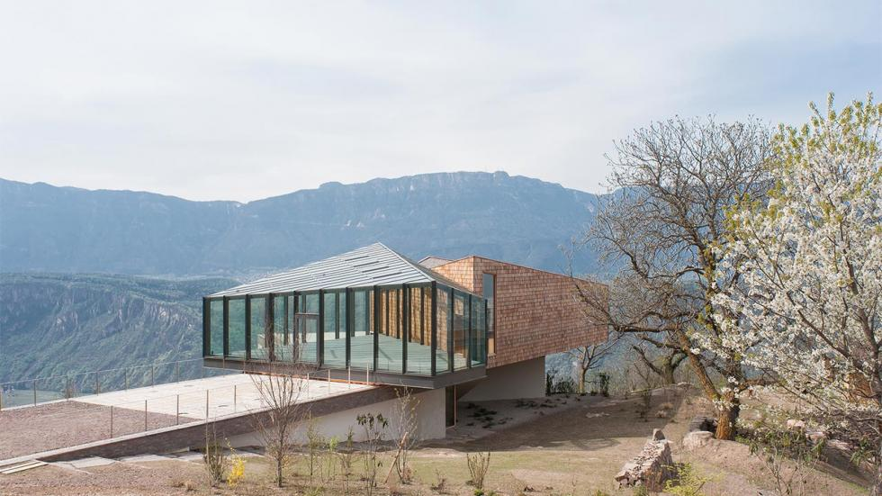 modern house made of wood and glass overlooking a valley