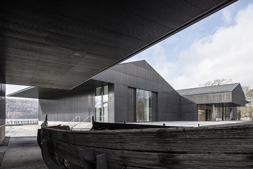 An image taken under the overhang of a modern museum building, whose siding is constructed from metal a dark matte metal siding