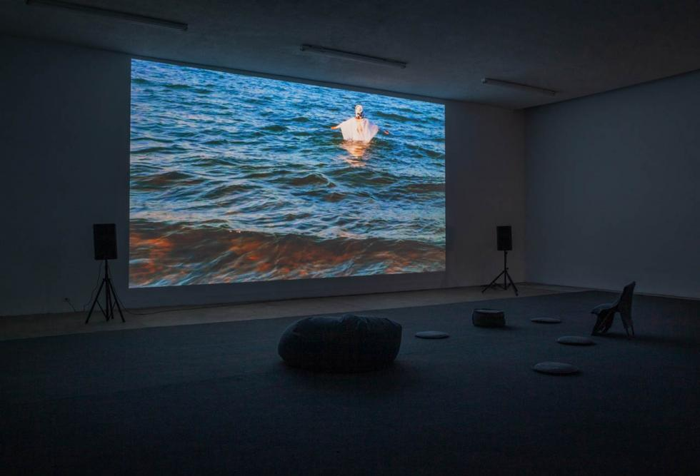 Film screened in a dark mostly empty room of a person dressed in white wading out into water.