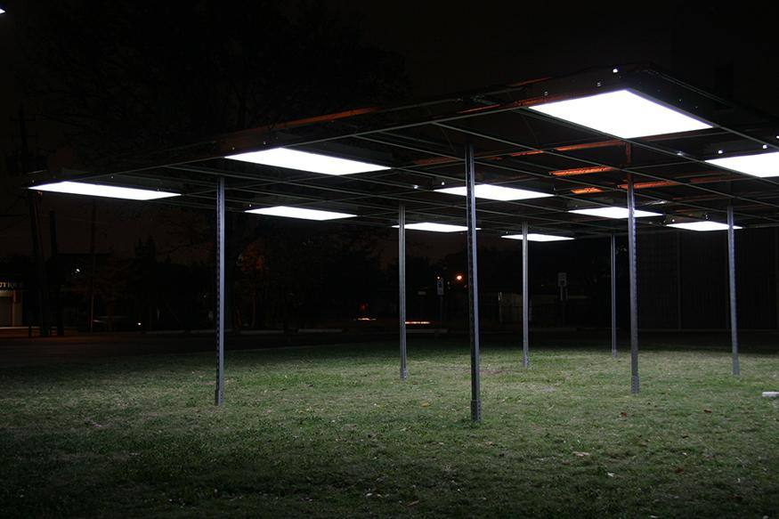 An outdoor installation in the form of a pavilion whose roof consists of a series of rectangular office lights