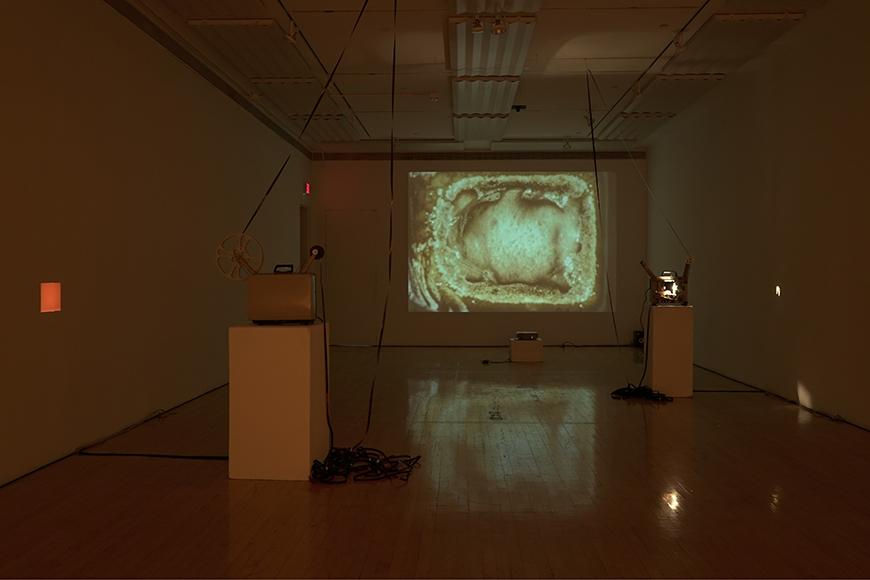 Image of projection with two projectors on pedestals.