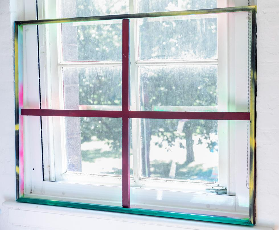 Painted window frame in pink, yellow, blue, green colors set against a white window overlooking a large tree.