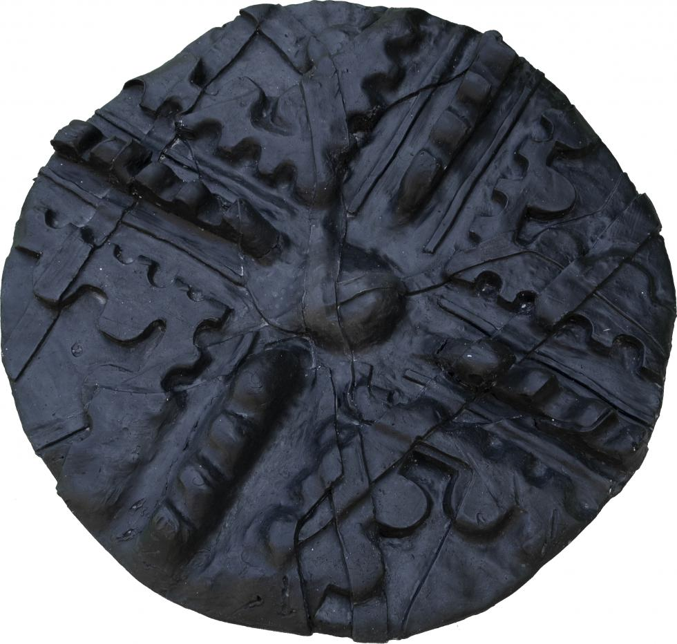 Black wax circle with a dome imprint in the middle, divided into 4 corner parts.