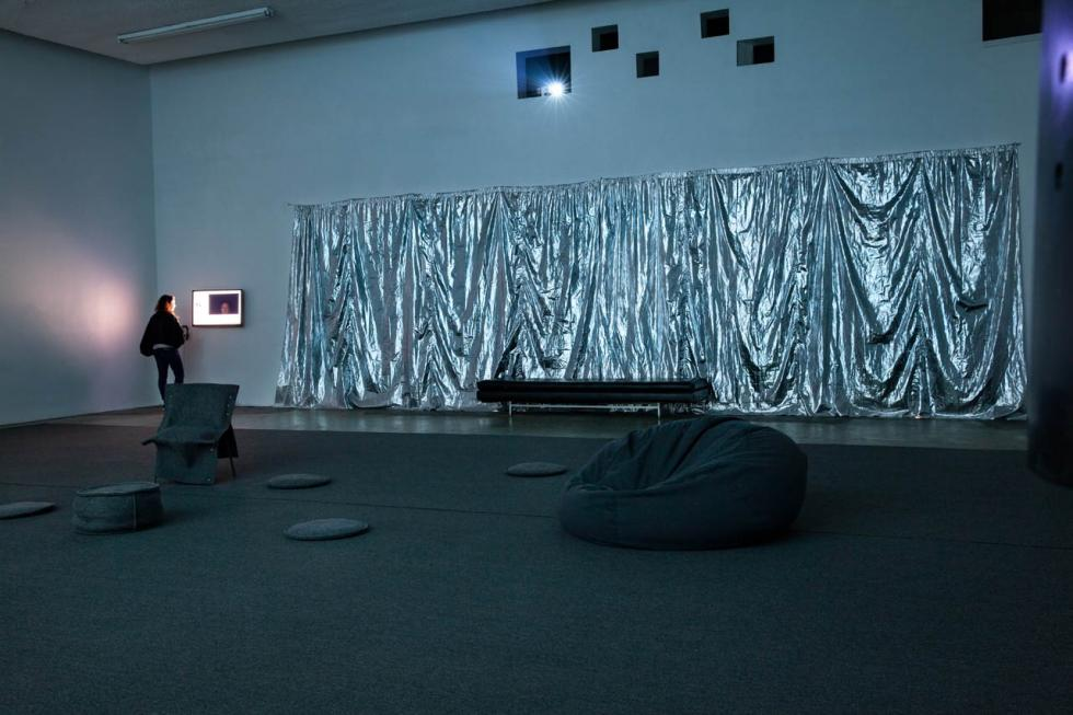 Silver wrinkled fabric hanging on a dark white wall in a room with dark carpet, bean bag, and one person looking at a small screen in corner.