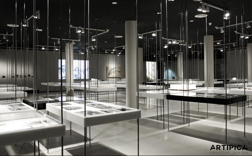 large room with white exhibition tables with photos on them and bars connecting them to the ceiling