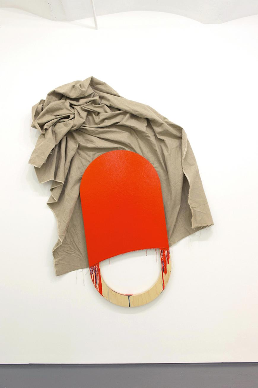 Tan fabric bunched up on a wall, partly hung behind an orange painted wooden abstract paddle.