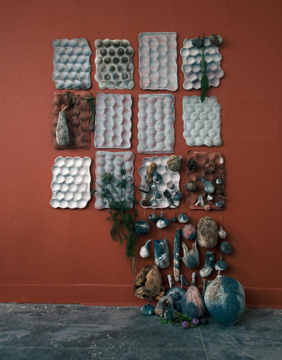 Dark red wall with 12 different colored gray egg cartons and randomly placed clay gourds hanging from them with larger clay gourds in the bottom left.