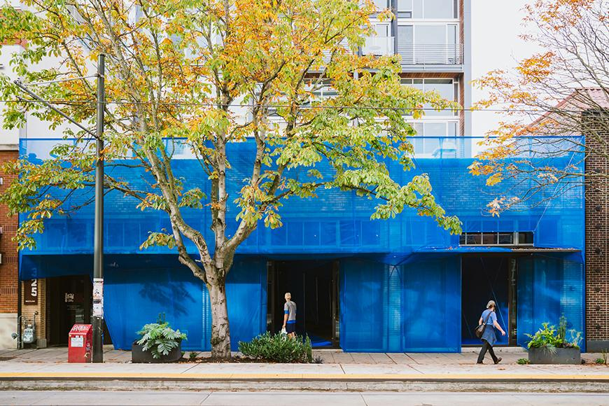 A blue facade constructed around the the front of a buildings exterior with people walking along a sidewalk next to an orange and yellow tree.