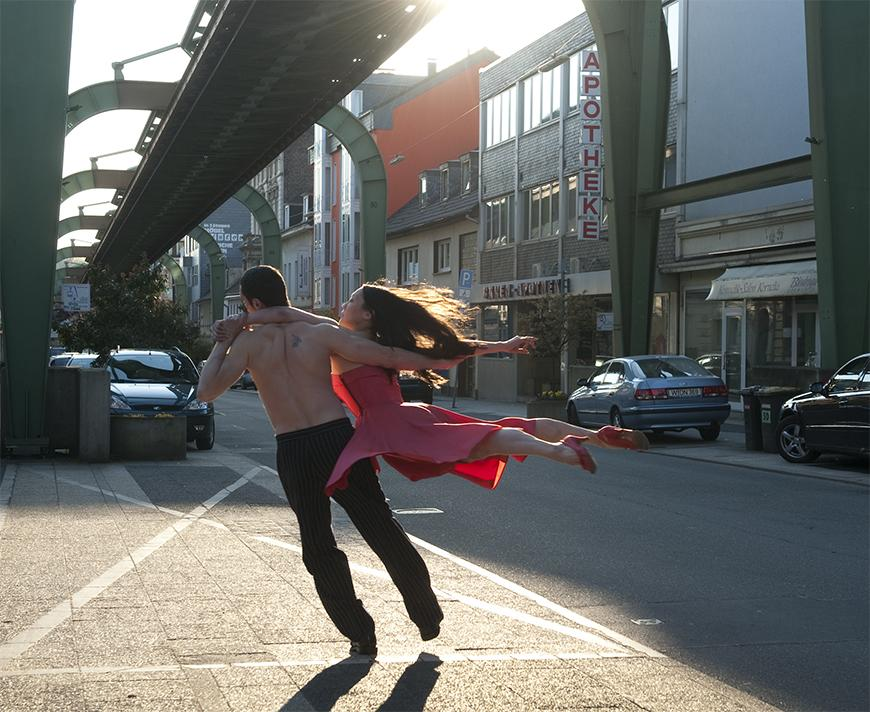 Two individuals dancing in the sunlight of a cityscape.