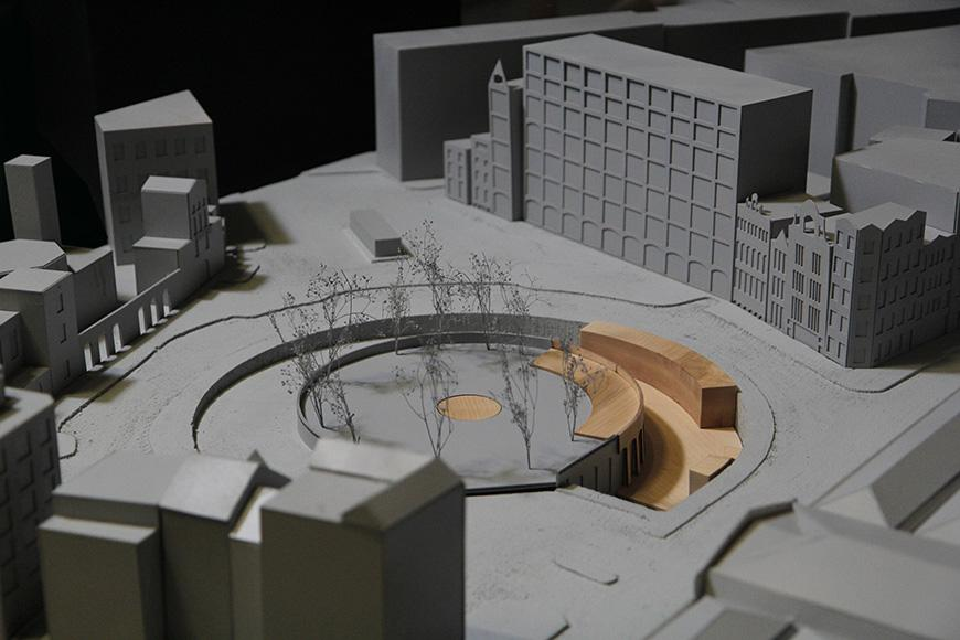 An architectural model with a round courtyard at its center surrounded by trees.