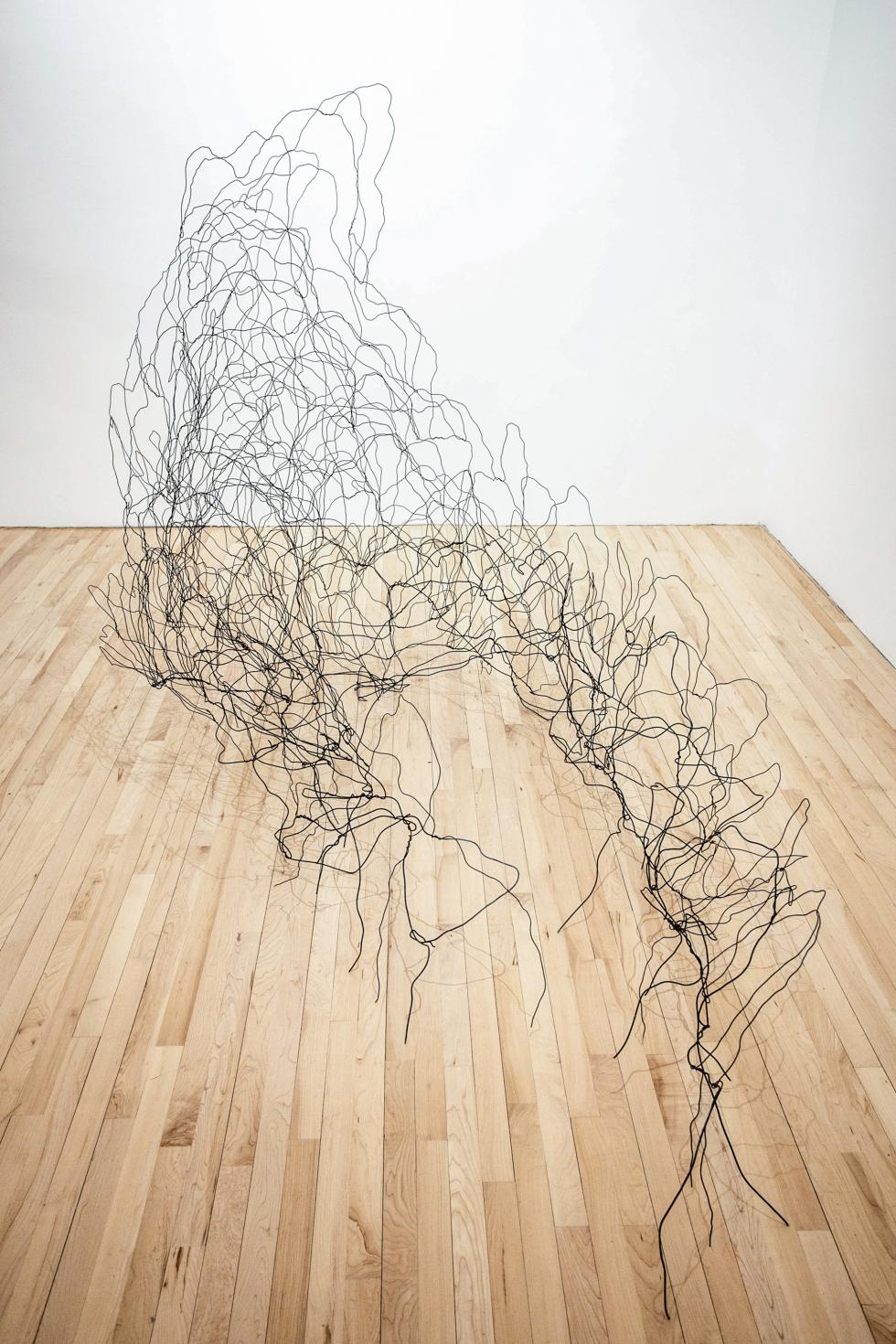 Large black wire sculpture in a loose hill pattern set against a white wall and light colored wooden floor.