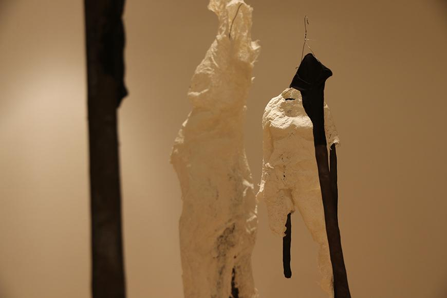 White fabric sculpture pieces placed on tall black clothes hangers.