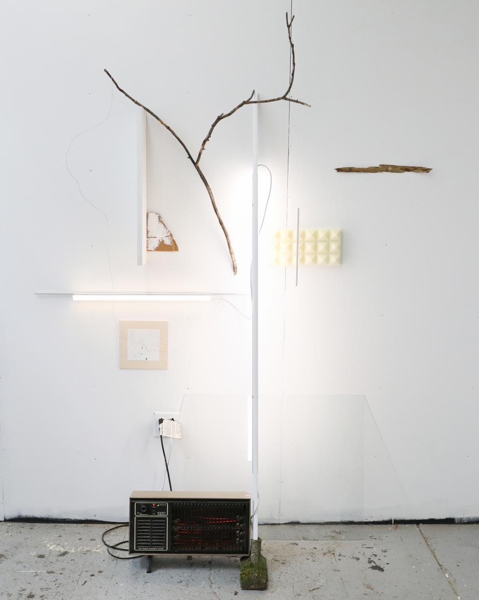 Space heater on the ground with LED lights, stick, bark, sound absorption foam, aluminum rod, and cardboard arranged on a white wall.