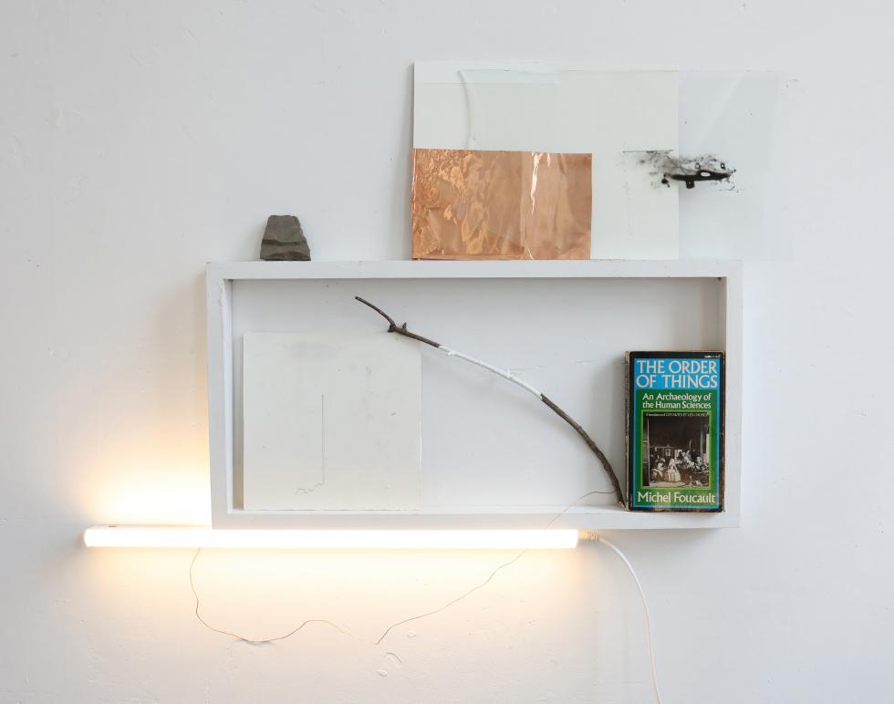 White open box on a white wall with a book, stick, copper foil stone, LED light arranged within, on top of, and beneath it.