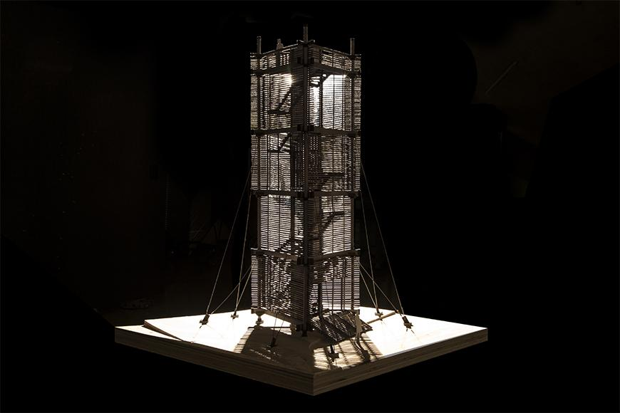Photograph of highly detailed wooden model of tower lit from the inside with black background.