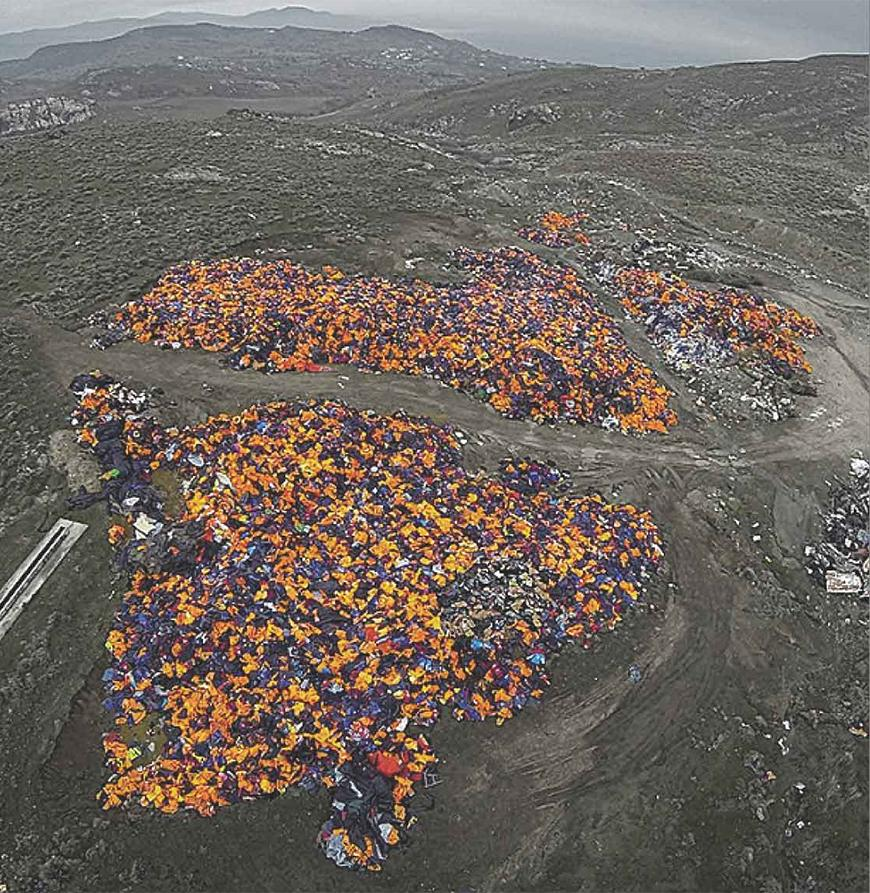 Color photograph of discarded life jackets on landfill-like dark mounds of dirt.