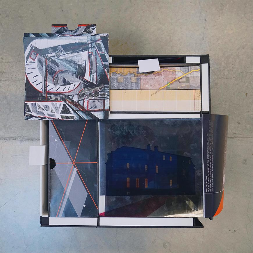 Photohraph of a box containing several drawings, transparencies, and fold-out images.