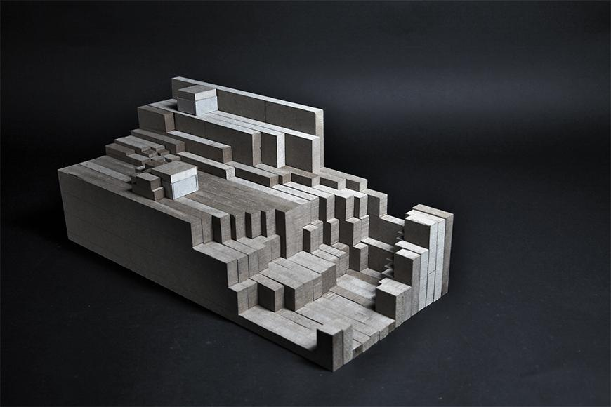Photograph of model made from frosted plexiglass and vertical sections of composite wood boards assembled together to form a topological mass.