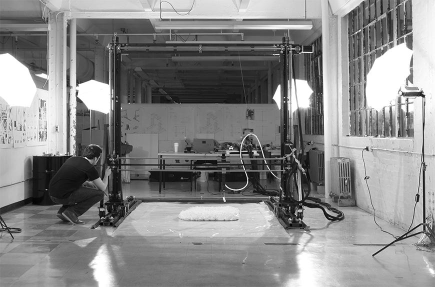 Black and white photograph of Chris Battaglia assembling 3D printer.