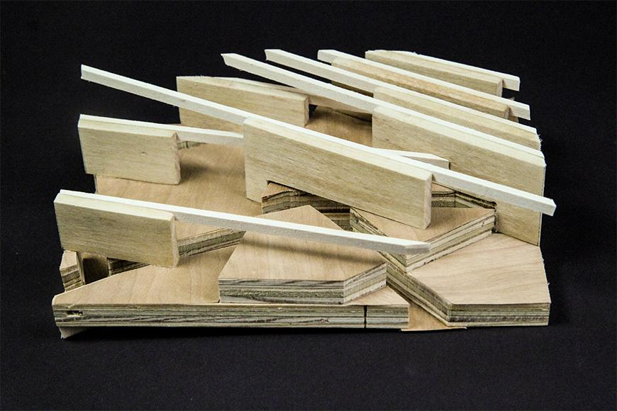 Photograph of section model made of layered plywood with slots and basswood and vertical pine boards arrayed diagonally on top of it.