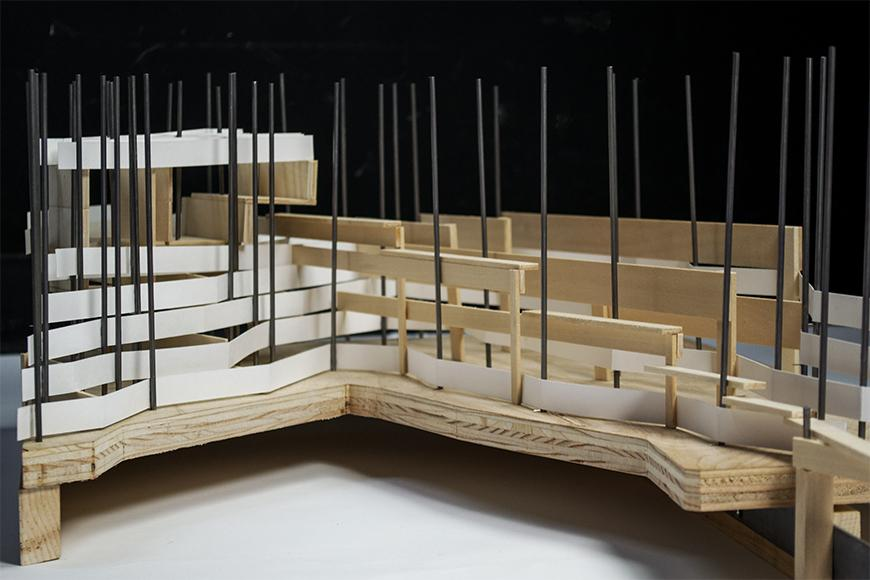 Photograph of part of a model made of a wooden plywood board as topography, with basswood structure on top and a large amount of vertical steel rods through which horizontal ribbons of white paper are woven.