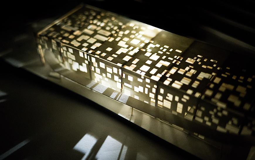 Photograph of paper model lit from the inside, so that light filters through perforated facade and cladding.
