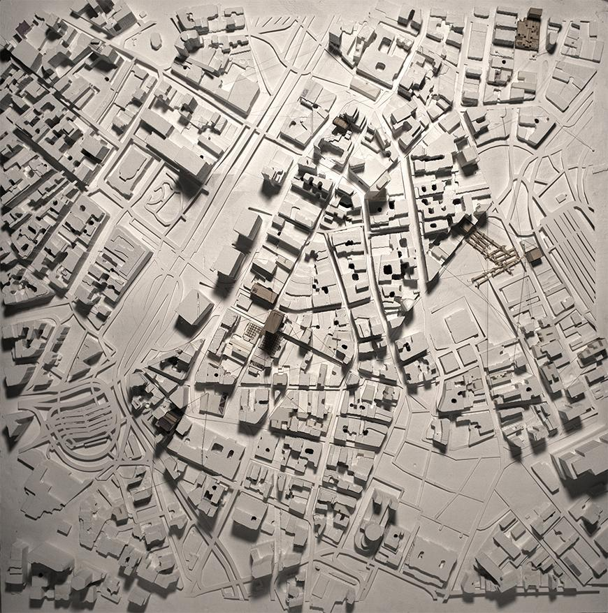 Photograph of white site model with places of intervation modeled in brown chipboard.