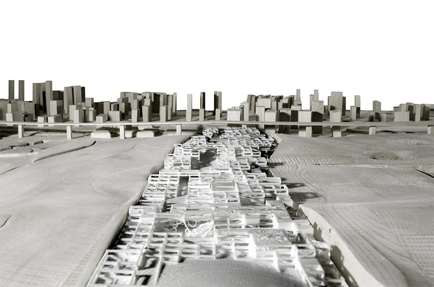 Photograph of white 3D printed model from above image placed into larger wooden site model, shot in a high-angle point of view looking down along the main axis of the model at a skyline in the background.