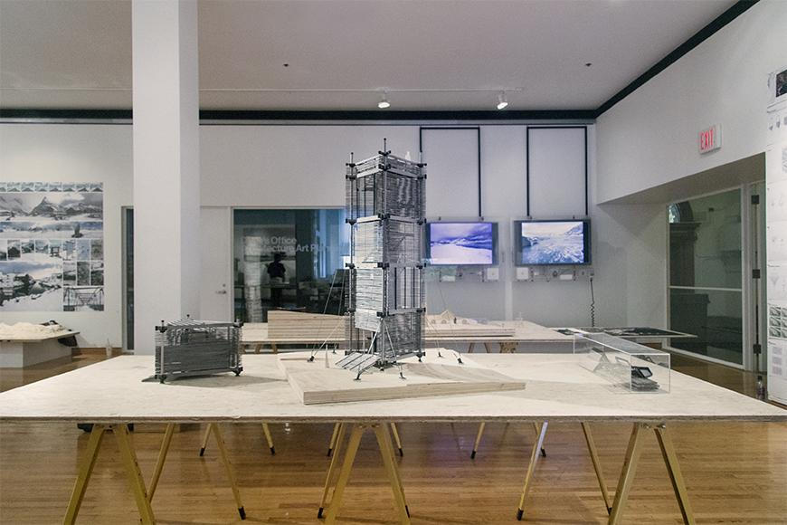 Photograph of detailed model of tower and study models on a plywood and metal table on exhibition in the Hartell Gallery of Sibley Hall.
