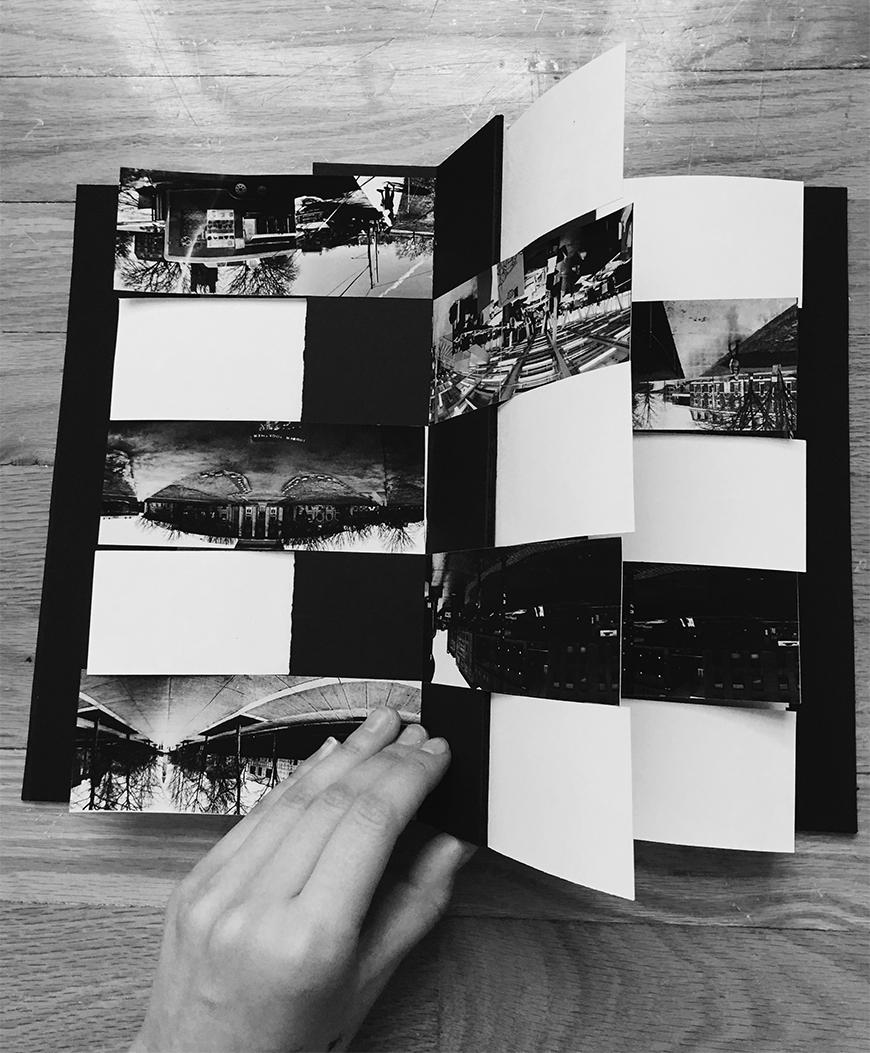 Photograph of booklet-like collage with images of spaces among black and white paper.s
