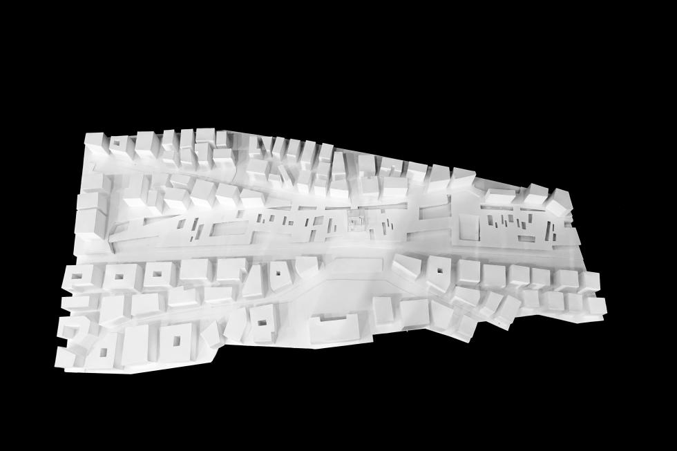 White model of the project within the site, seen  from above on a black background.