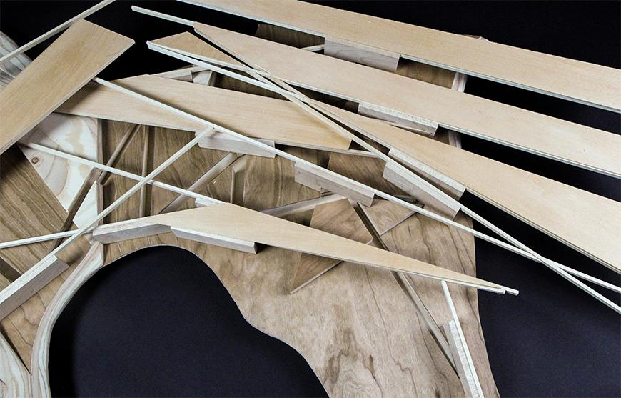 Photograph of part of model made of milled wood with slots cut into it and thin plywood and basswood set into the slots.