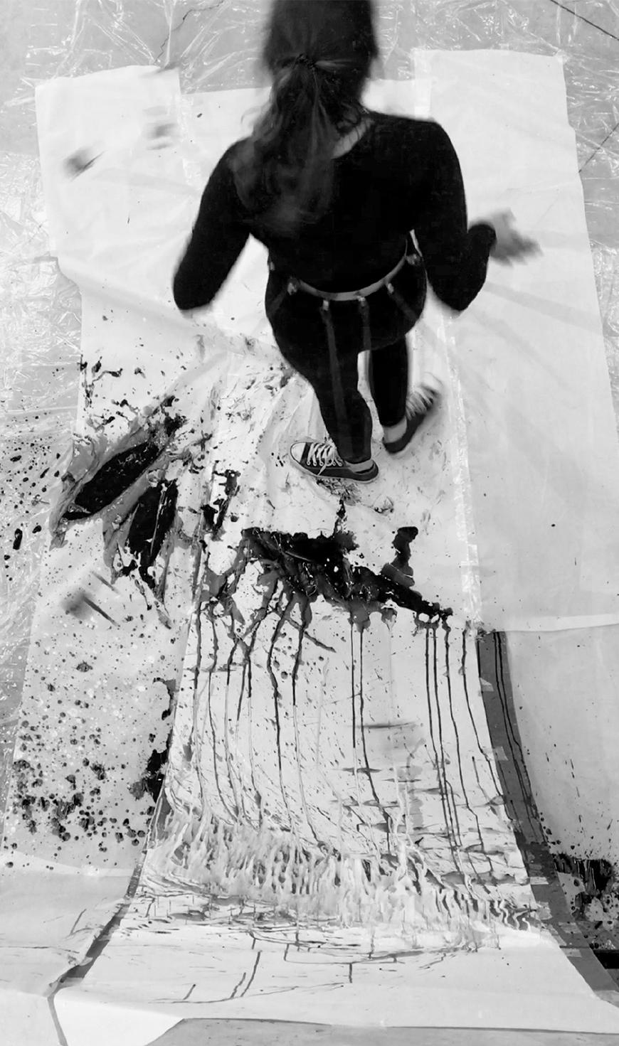 Black and white photograph of drawing machine being operated by a person, seen from above as gravity has made its effect o the ink and the drawing is nearly finalized.