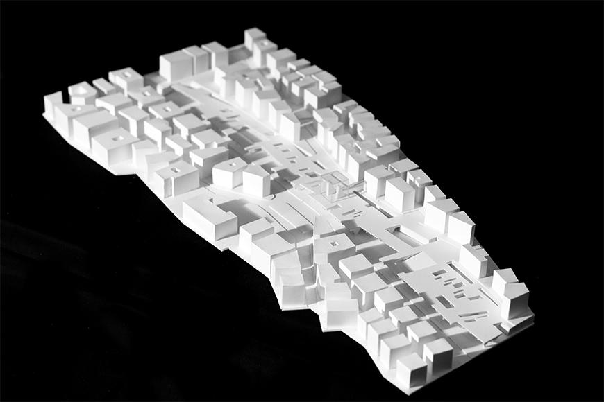 White model of the project within the site, seen in aerial perspective.