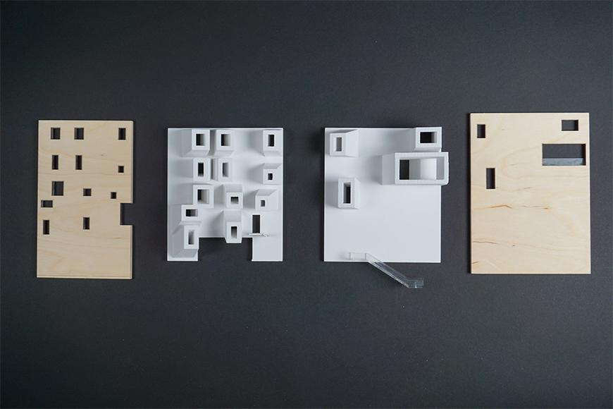 Photograph of wall components for project model showing wooden boards for the exterirors and a matte white material for the interior walls.