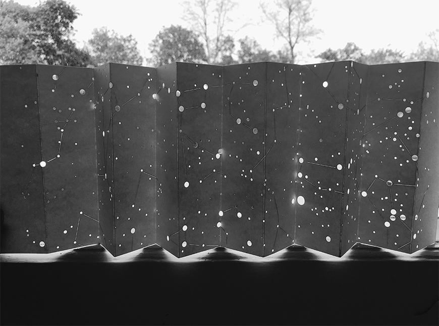 Black and white photograph of map made on pleated paper surface by creating holes to indicate the placement of stars, placed against a window so that light comes in through the openings.