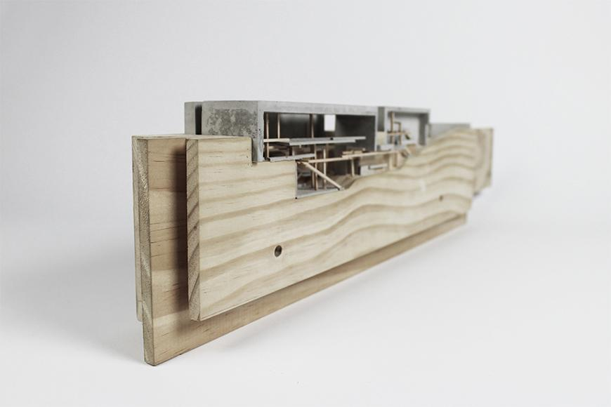 Photograph of model made with vertical wooden boards as the site with rockite boxes set into the top of the boards and basswood sticks representing interior structure.