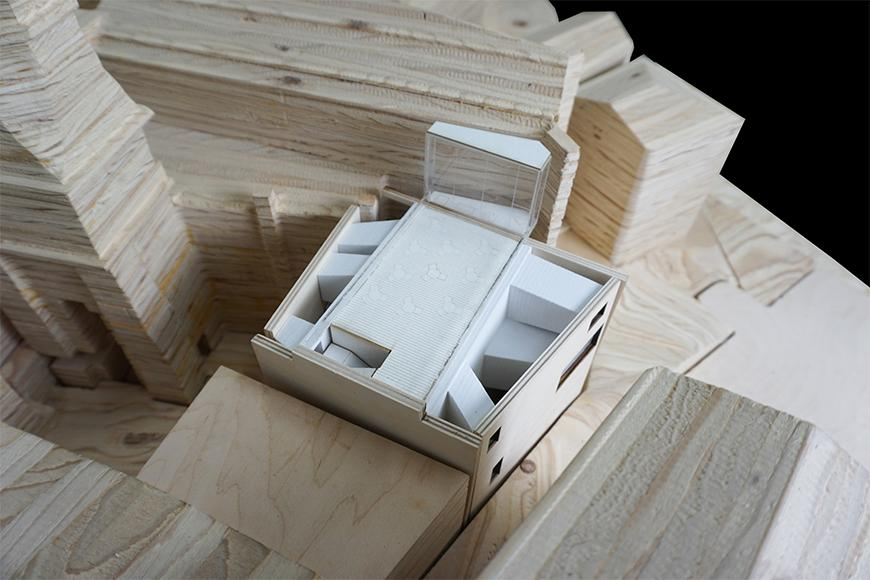 Photograph of previous model inserted into site model cut from stacked plywood, seen from aerial perspective.