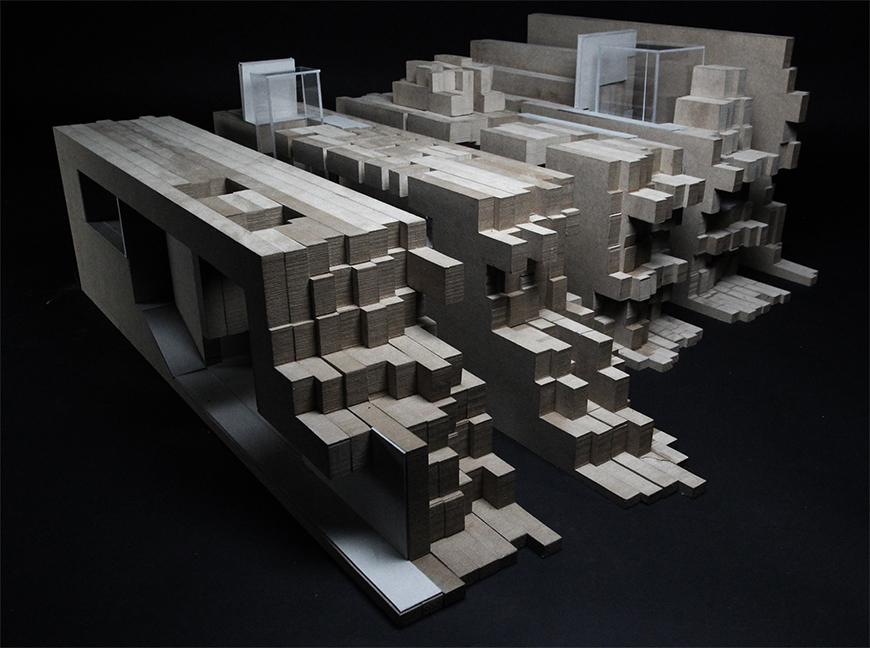 Photograph of model made from paper, basswood, and chipboard layered together into vertical sections of chipboard assembled into a topological mass.