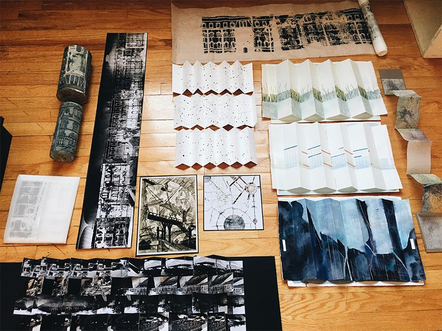 Photograph of set of drawings and images in different mediums, some folded, laid out on a wooden floor.