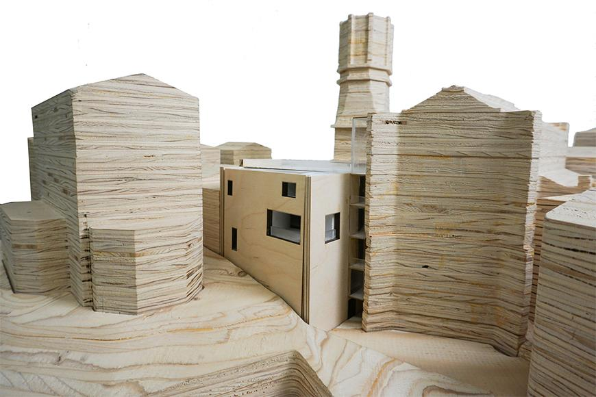 Photograph of previous model inserted into site model cut from stacked plywood, seen from the side.