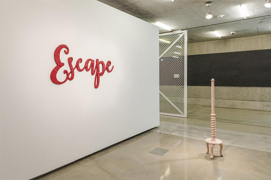 White wall to the left with the word 'Escape' written in red cursive letters next to a tan unfinished coat rack.
