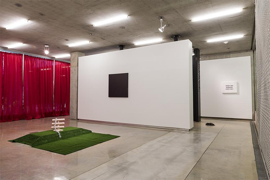 Red curtains in the back left, green turf with an abstract wooden sculpture on it, a white wall with a square dark image and another white wall with a small white sign with black letters.