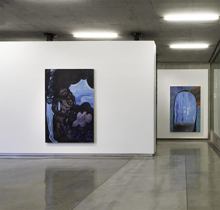 Two white walls staggered to reveal two abstract paintings in various blue, black, brown, purple, and orange hues.