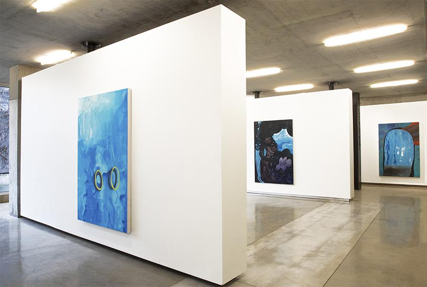 Three white walls staggered to reveal three abstract paintings on each end.