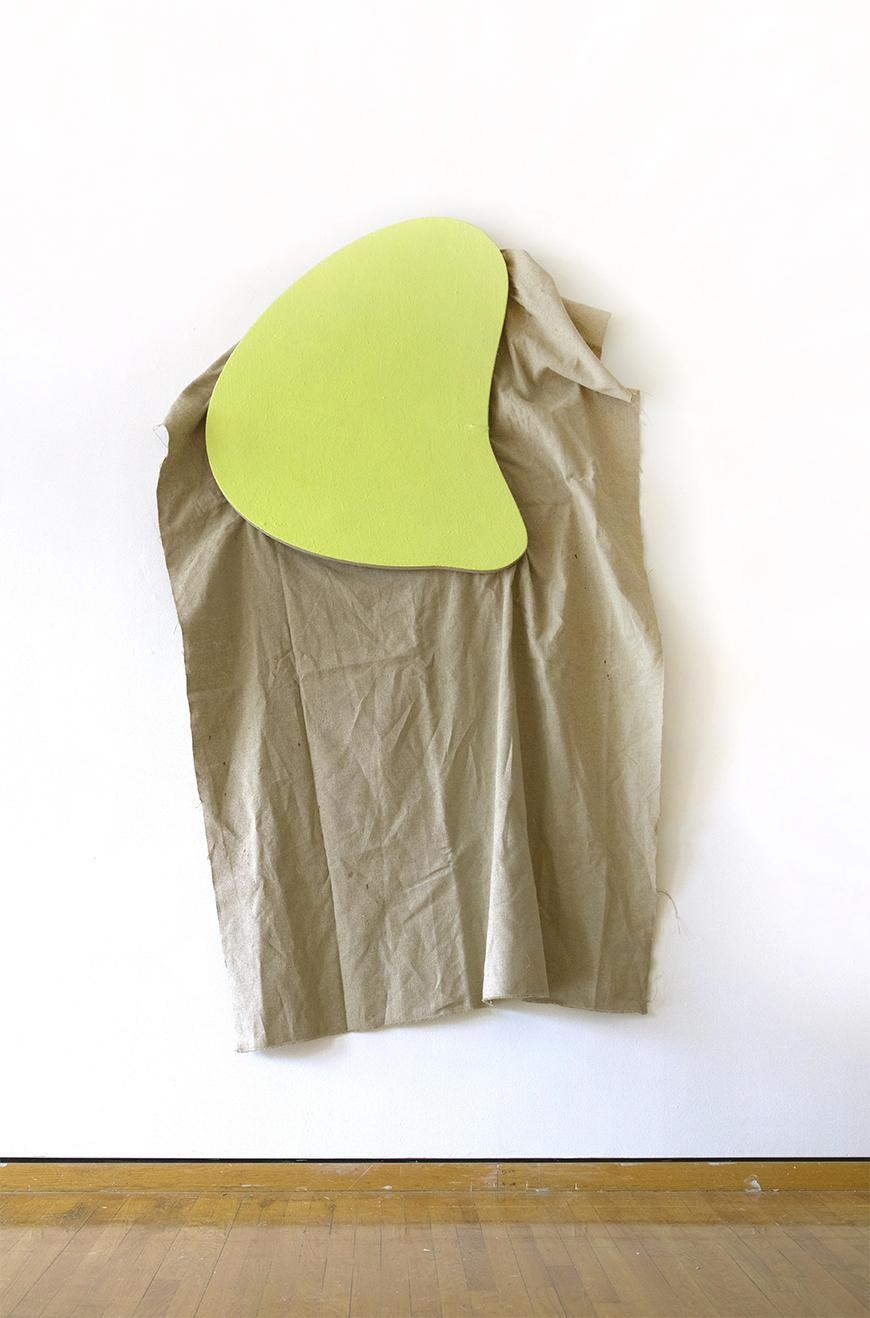 Tan colored fabric hung from a white wall with a yellow green abstract shape holding it up.