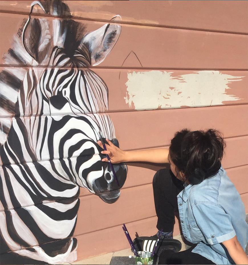 Woman in a light blue blouse and black pants painting a zebra mural on a light red paneled building.