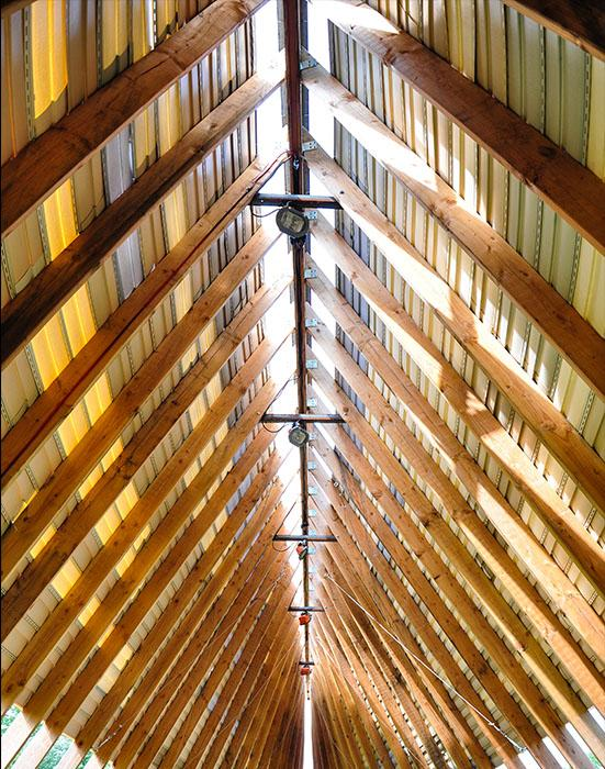 steeply pitched roof with approximately 40 wooden rafters seen from inside